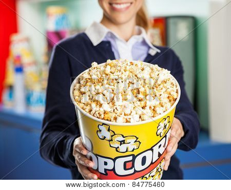 Midsection of smiling female worker offering popcorn bucket at cinema concession stand