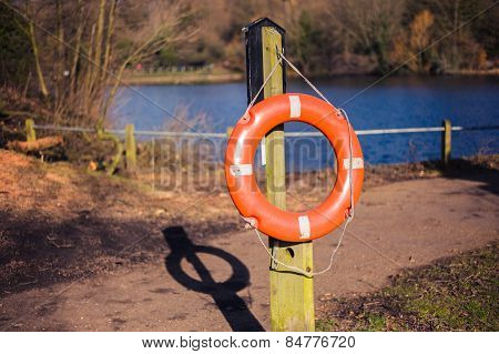 Lifebuoy On Wooden Post In Park