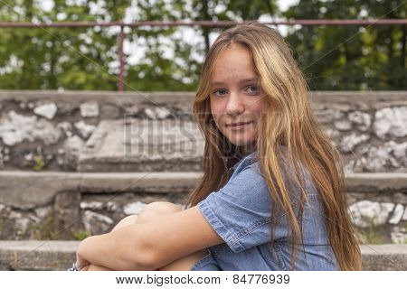 Portrait of young girl sitting on the stone steps at the old city Park.