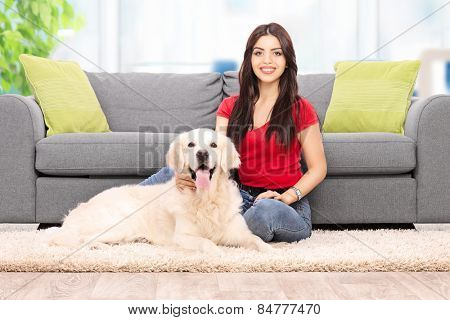 Young woman sitting by a sofa with her dog at home