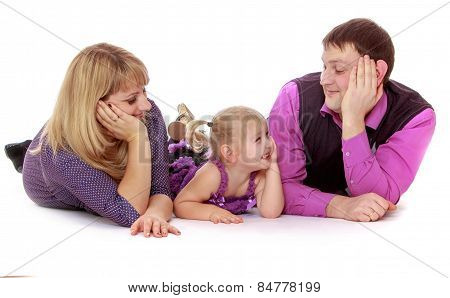 happy young family lying on the floor and looking at each other