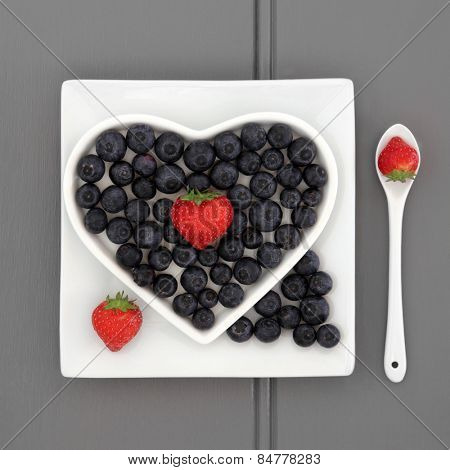 Blueberry and strawberry antioxidant fruit in a heart shaped dish on a square plate with porcelain spoon.