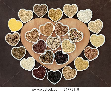 Grain and cereal food selection on a heart shaped wooden board and in porcelain bowls over lokta paper background.
