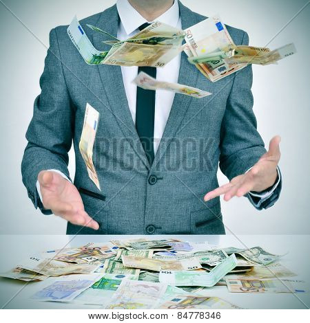 man in suit trying to catch money falling from the sky