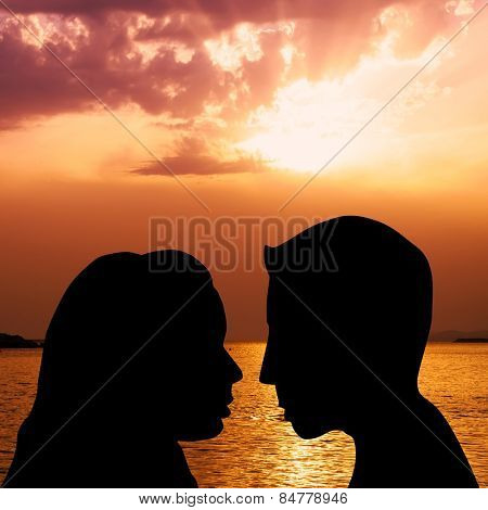 Silhouettes of couple kissing on the beach at sunset