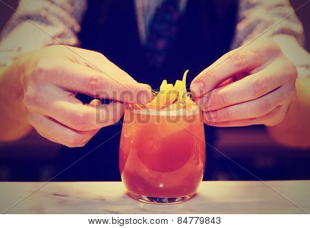 Barman is decorating cocktail with lemon zest, toned image