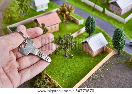 Man's Hand With Key From Country House In Village