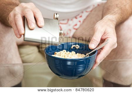 Alcoholic spiking his cereal with vodka from a flask.  Shallow depth of field with focus on the pouring alcohol.