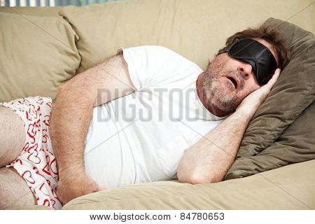 Lazy man at home in his underwear, sleeping on the couch and snoring.
