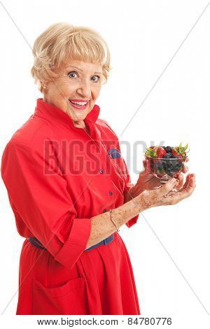 Fit senior woman snacking on a bowl of healthy mixed berries.  Isolated on white.