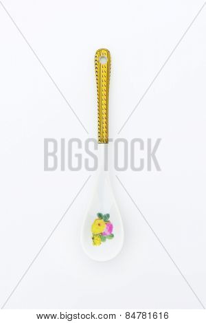 White spoon with floral and ornate print