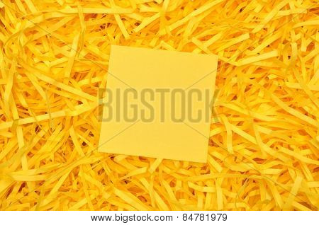 Yellow sticky note on shredded paper