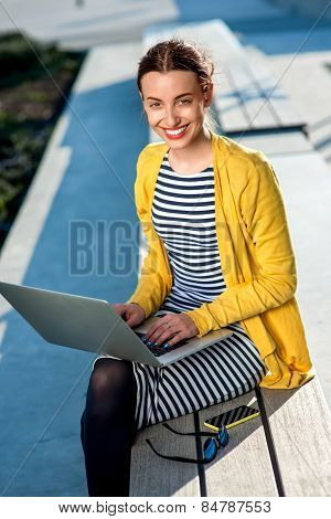 Woman with laptop and phone outdoors