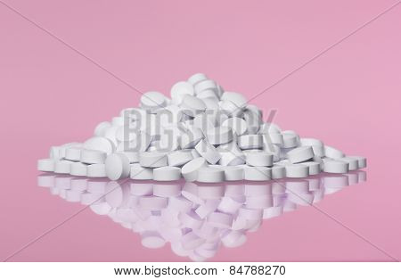 Stack of pills towards pink background