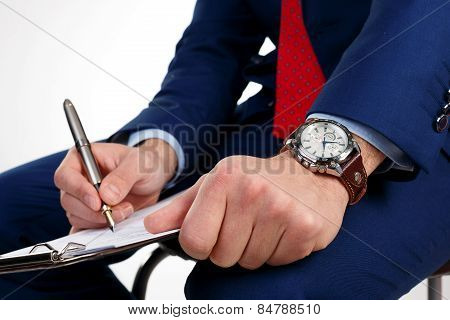Businessman with a clock on the hand writes the document.