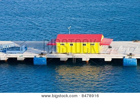 Yellow Building With Red Roof On Pier