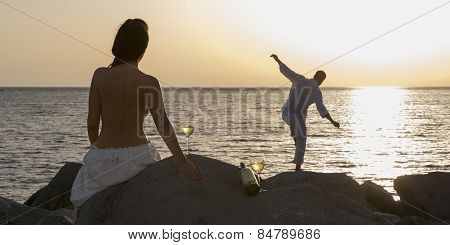 Silhouette of young attractive couple at sunrise on beach rocks