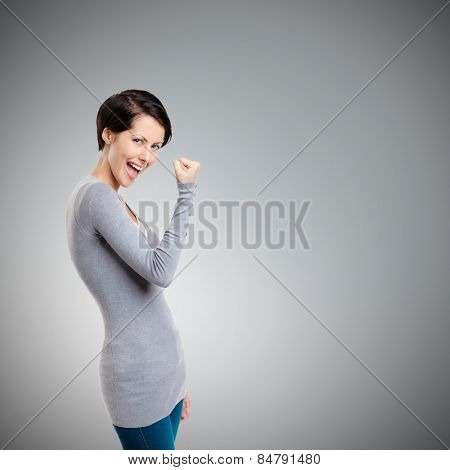 Young happy girl gestures fist, isolated on grey