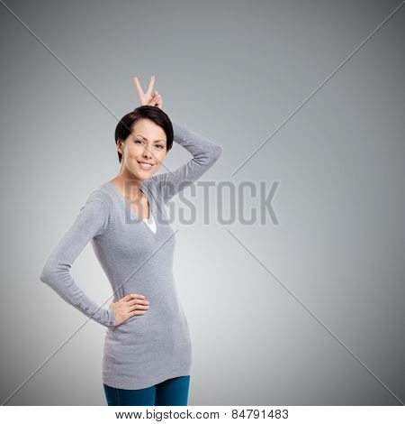 Wonderful girl gestures hand horn to herself, isolated on grey