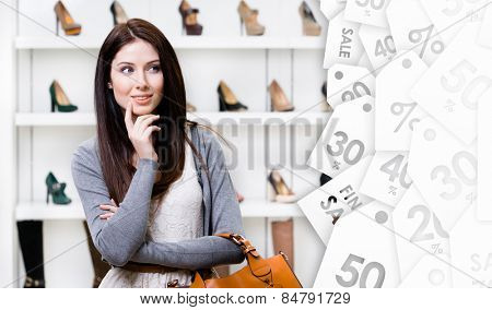 Woman in shopping center in the section of female stylish shoes, clearance sale. Concept of consumerism and stylish purchase