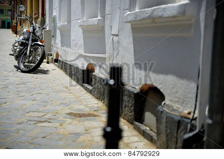 Parked Motorcycle In An Alley