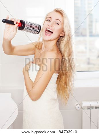 Woman in the morning at bathroom. Funny female sing song in comb