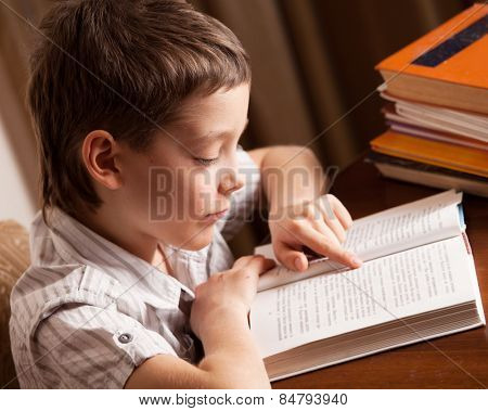 Boy reading book at home. Child education