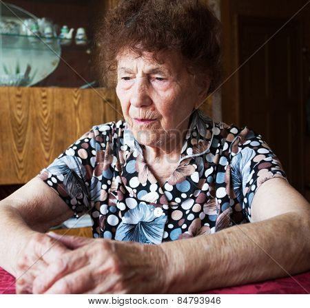 Old woman. Elderly sad female at home. Sorrow