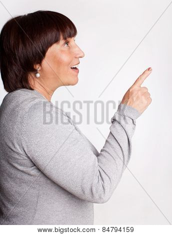Mid woman showing a finger in the direction. Isolated on gray