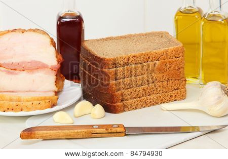 Sliced Bread,bacon And Olive Oil On White Kitchen Table.