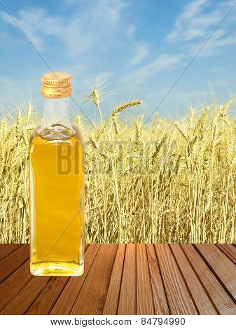 Vegetable Oil On Wooden Surface Against Of Yellow Wheat Ears.