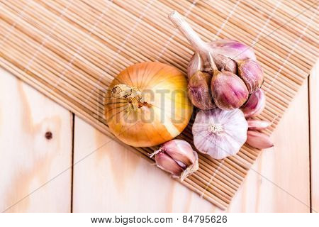 clove of garlic and bulb onion on wooden background