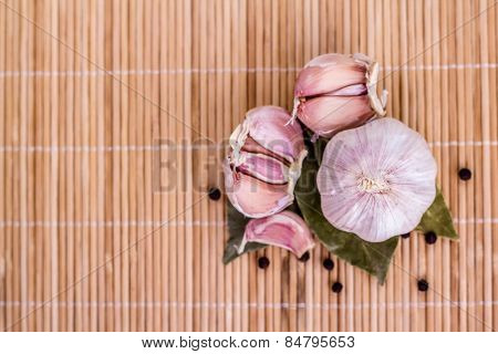 clove of garlic and bay leaves on wooden background.