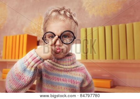 Little girl in glasses makes faces