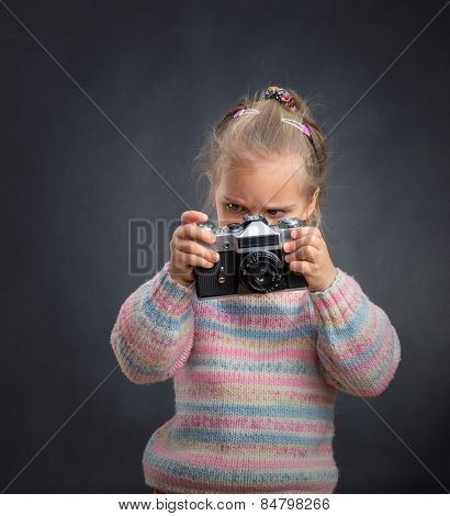 Little cute girl looks photos at the camera