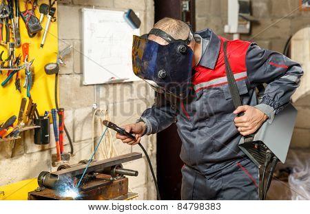 Welder worker in protective mask welding metal
