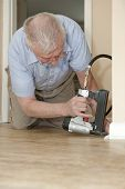 image of baseboard  - A senior man on his hands and knees - JPG
