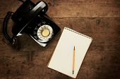 Постер, плакат: Note pad or memo pad and an old dial telephone on an grungy wooden board or surface For inserting y