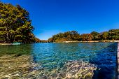 stock photo of crystal clear  - Bright Beautiful Fall Foliage Surrounding the Swimming Hold in Garner State Park on the Crystal Clear Frio River - JPG