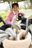 foto of buggy  - Happy golfer driving his golf buggy smiling at camera at the golf course - JPG