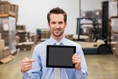 pic of warehouse  - Warehouse manager showing tablet pc smiling at camera in a large warehouse - JPG