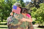 stock photo of reunited  - American soldier reunited with daughter on a sunny day - JPG