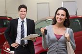 picture of showrooms  - Female driver showing a key after bying a new car at new car showroom - JPG