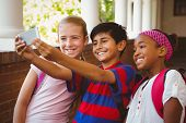 stock photo of little school girl  - Portrait of happy little school kids taking selfie in school corridor - JPG