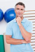 stock photo of thoughtfulness  - Thoughtful man posing with hand on chin in fitness studio - JPG