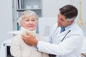 pic of neck brace  - Male doctor examining senior patient wearing neck brace in clinic - JPG