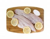 stock photo of catfish  - Fresh catfish fillets on a cutting board with lemon and isolated on  white - JPG
