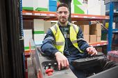 foto of forklift driver  - Smiling driver operating forklift machine in warehouse - JPG
