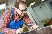 foto of chisel  - carpenter installer works with hammer and chisel at interior wood door installation - JPG