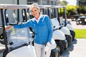 stock photo of buggy  - Female golfer beside golf buggy at the golf course parking - JPG